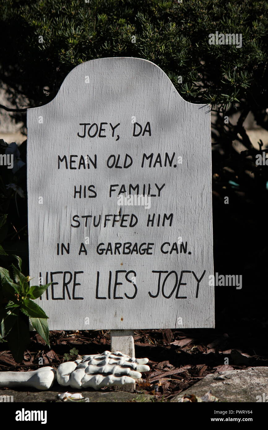 Handmade tombstone Halloween lawn decoration with a scary epitaph 'Joey da mean old man, his family stuffed him in a garbage can, here lies Joey' - Stock Image