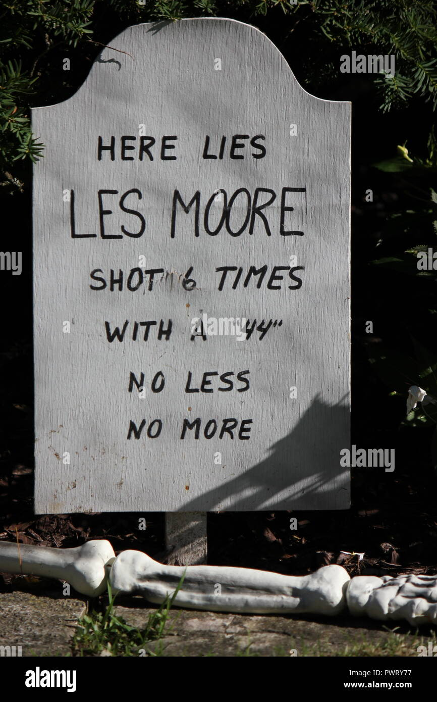 Handmade handwritten tombstone Halloween lawn decoration with a scary epitaph 'Here lies Les Moore, shot 6 times with a '44' no less no more' - Stock Image