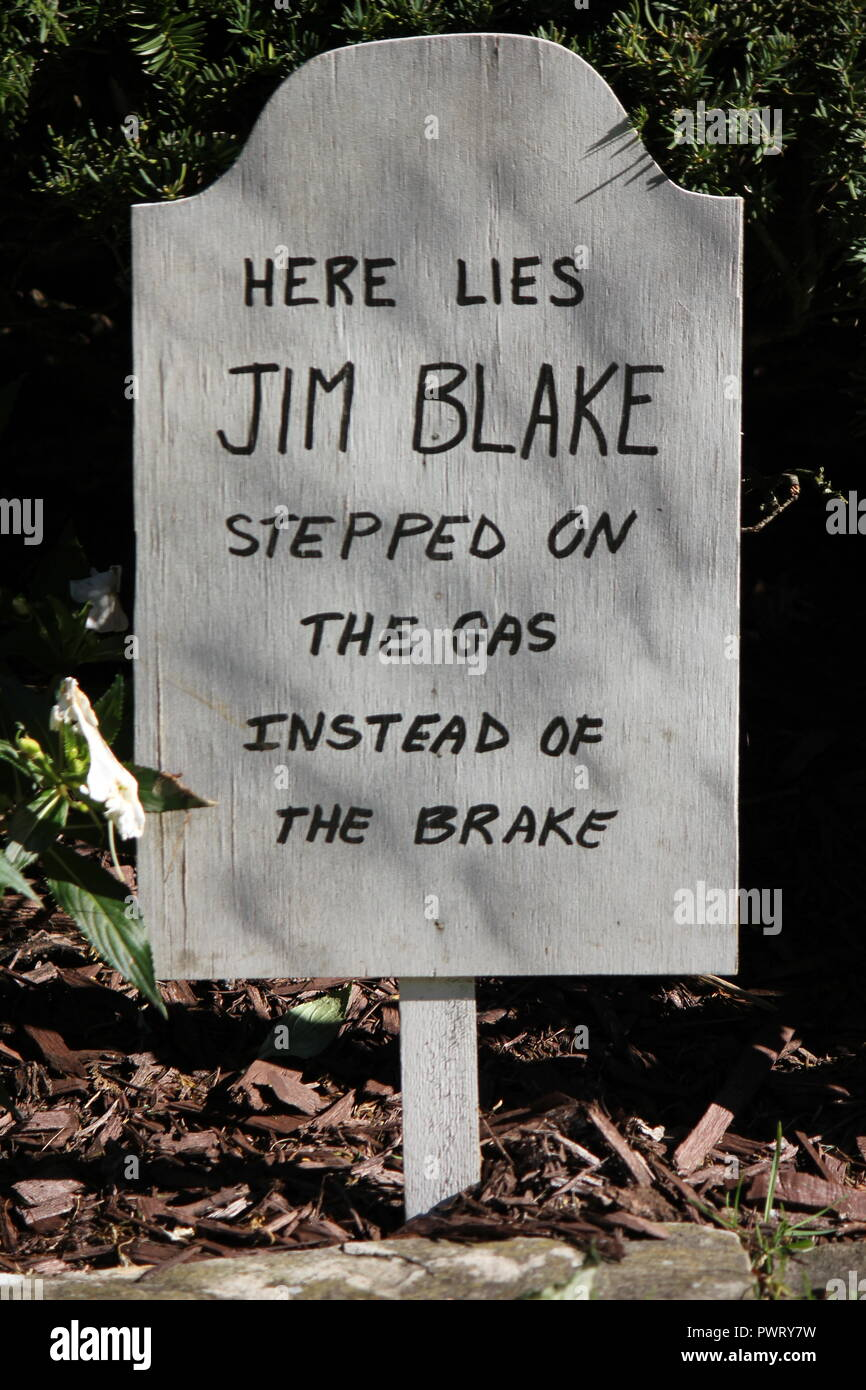 Handmade handwritten tombstone Halloween lawn decoration with a scary epitaph, 'Here lies Jim Blake stepped on the gas instead of the brake' - Stock Image