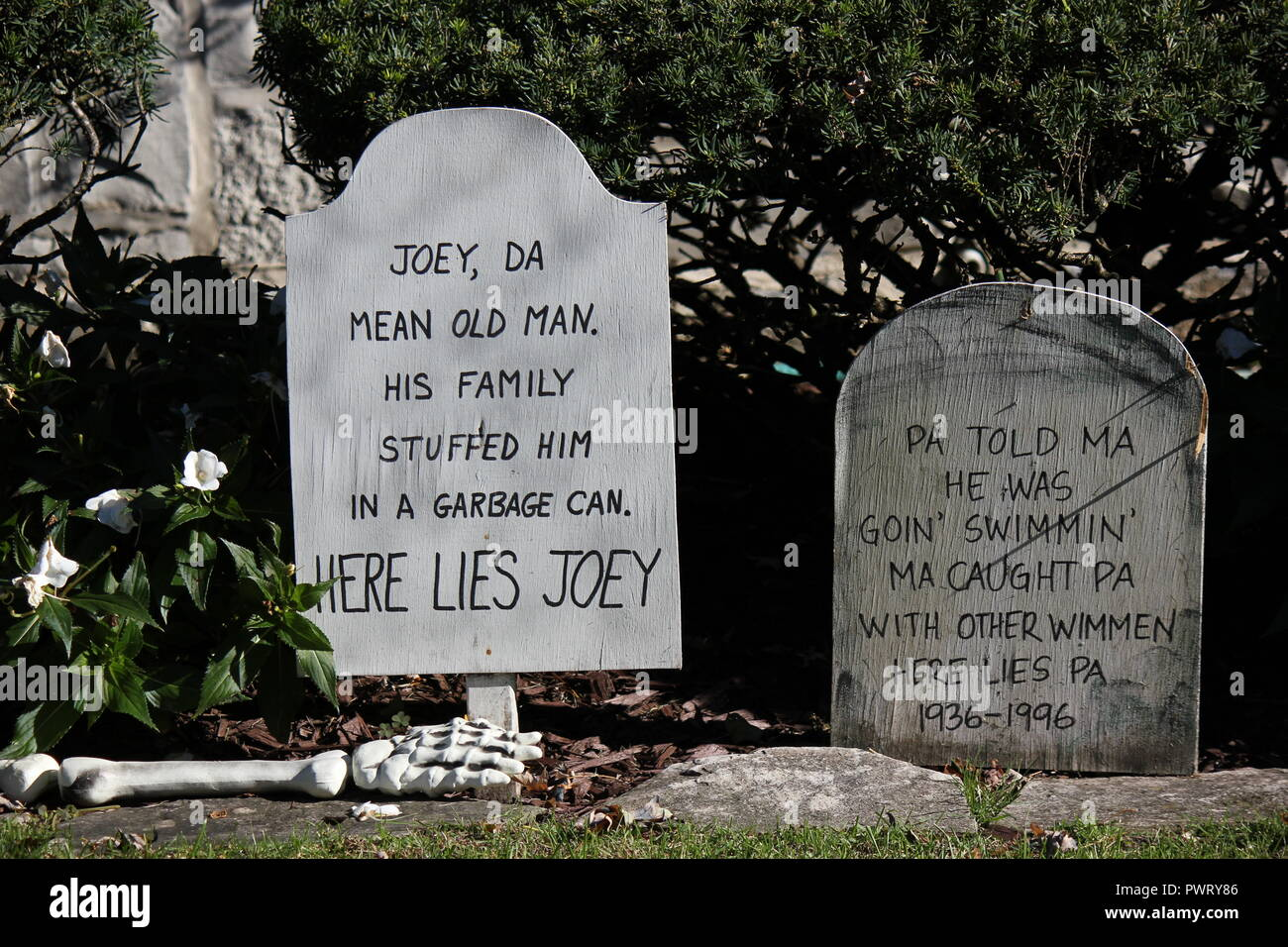 Two Handmade handwritten tombstones posing as Halloween lawn decorations with a scary epitaph. - Stock Image