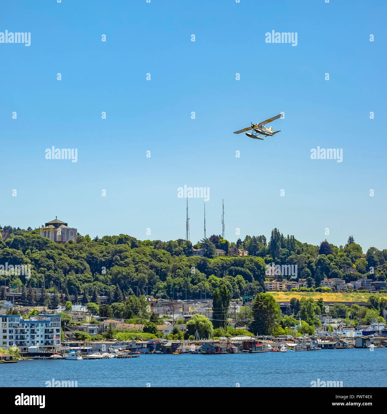 Float plane flying over Union Lake and city - Stock Image