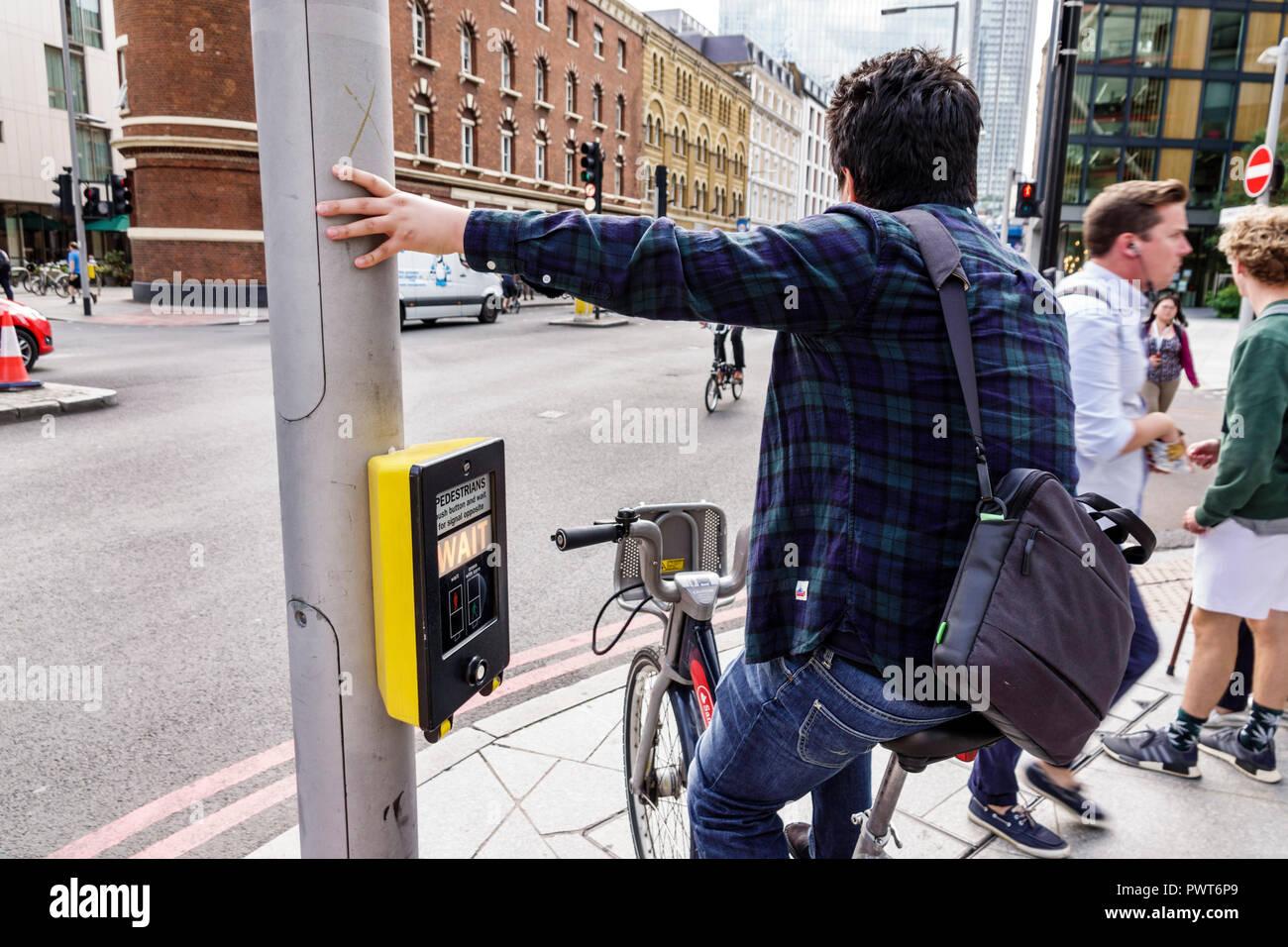 London England United Kingdom Great Britain Southwark street pedestrian crossing crosswalk signal activation box cyclist bicycle man rider waiting tra - Stock Image