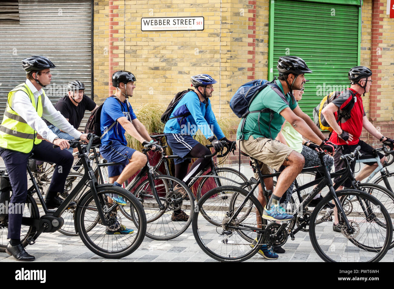 London England United Kingdom Great Britain Lambeth Webber Street bicycle bike lane work commuters riding riders bicycles helmets man rush hour traffi - Stock Image