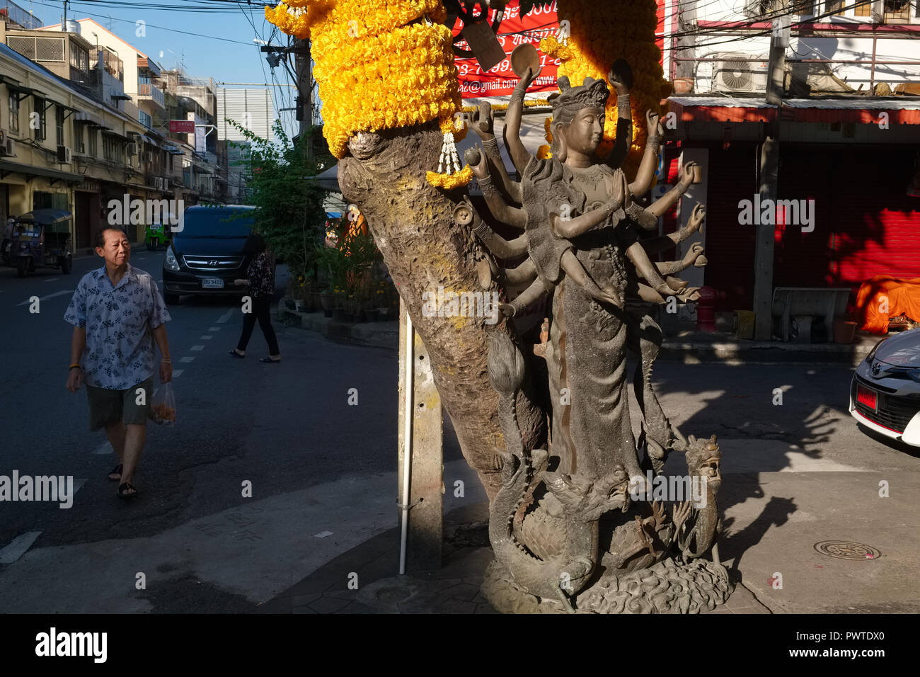 A man walking past the statue of a Taoist goddess in Bamrung Muang Rd., Bangkok, location of factories and shops for religious and devotional objects - Stock Image