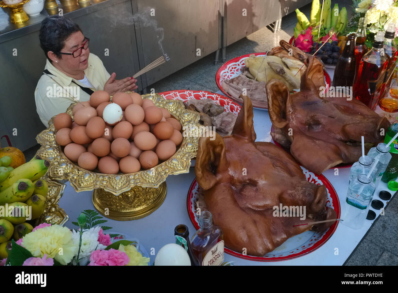 A woman prays at Lak Mueang or City Pillar Shrine in Bangkok, Thailand, where the city's guardian spirit is appeased with boiled eggs and pigs' heads - Stock Image