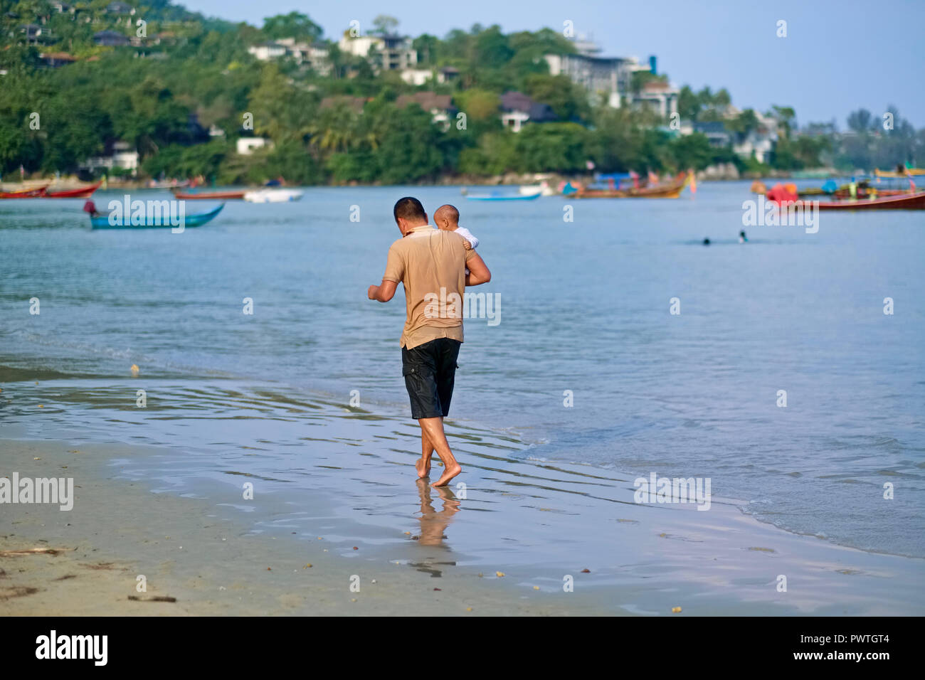 A man at Kamala Beach, Phuket, Thailand, proudly takes his young child for a walk along the sea - Stock Image