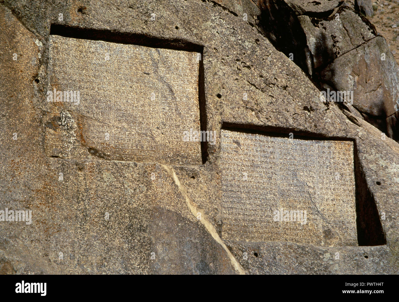 Ganjnameh. Ancient inscription carved in granite in Alvand Mountain, ordered by Darius the Great (521-485 BC) (left) and by Xerxes the Great (485-465 BC) (right) in three languages, Old Persian, Neo-Babylonian and Neo-Elamite. Near Hamedan. Islamic Republic of Iran. - Stock Image