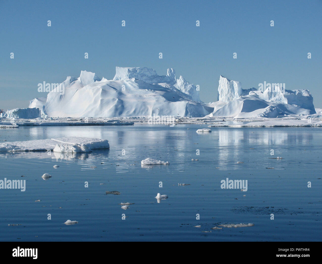 Ice tip of the iceberg, the age-old ice, the sun shines through. Close-up. Antarctica. - Stock Image