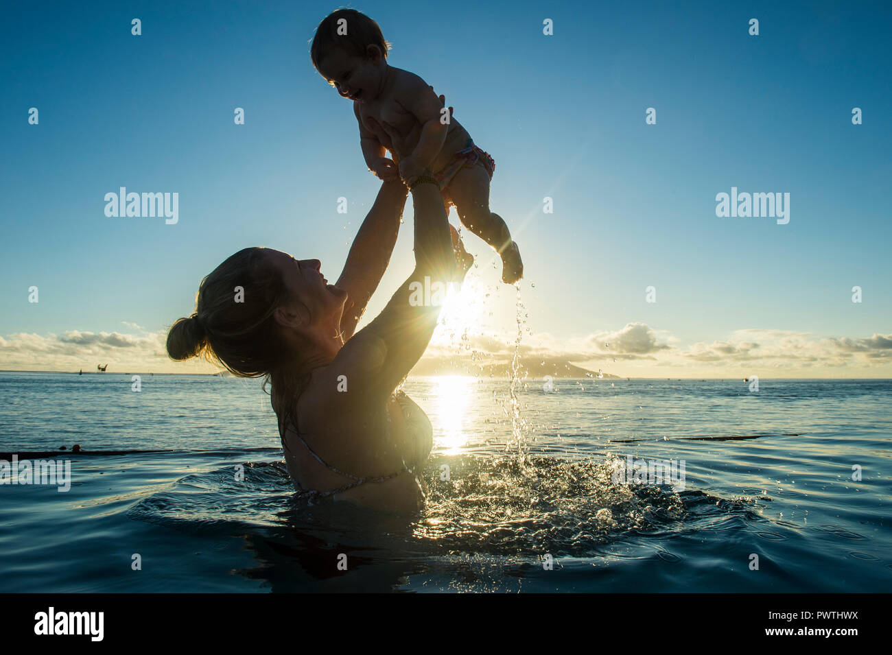 Mother playing with her little baby in the water at sunset, Papeete, Tahiti - Stock Image