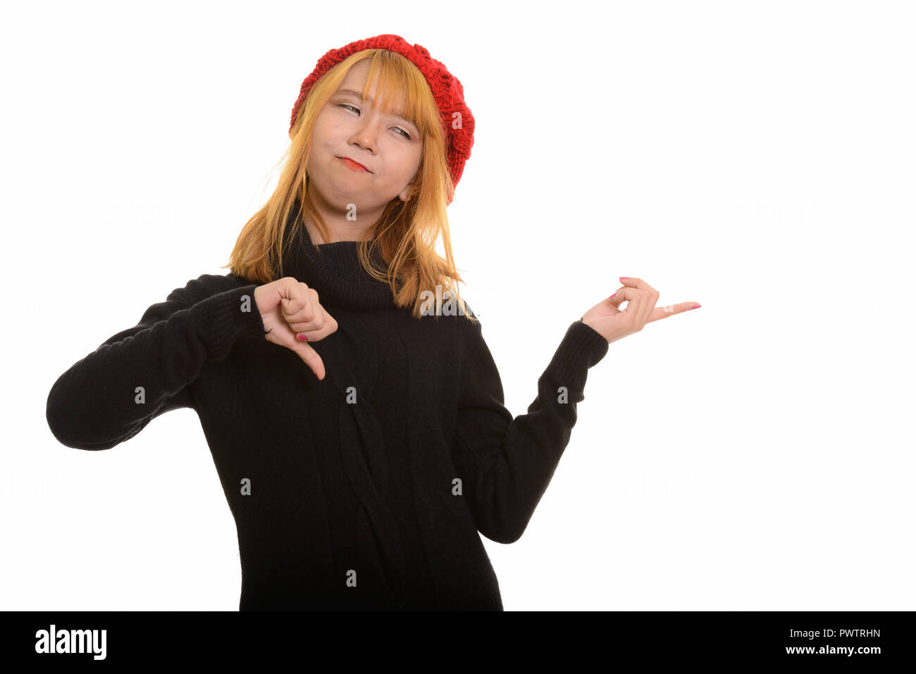 Young cute Asian woman giving thumb down and pointing finger at  - Stock Image