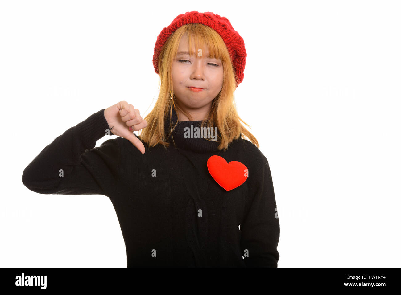 Young cute Asian woman giving thumb down with red heart on chest - Stock Image
