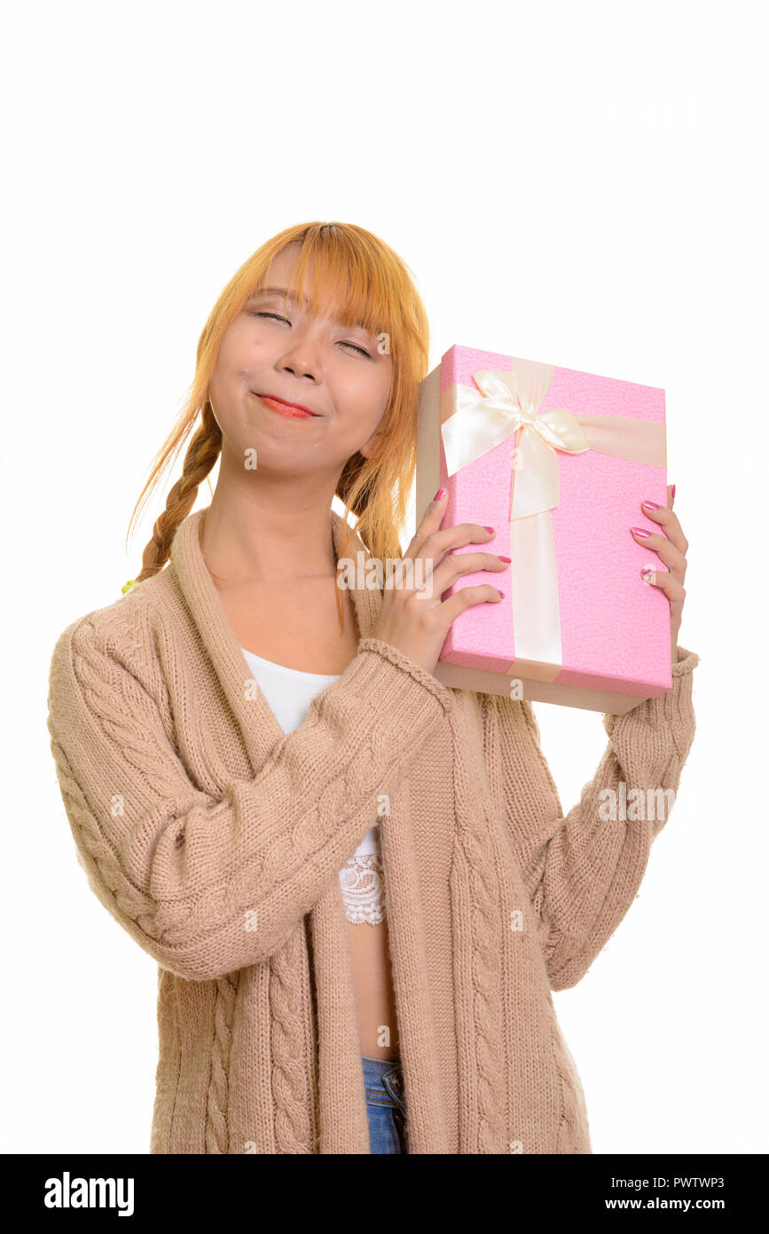 Young thoughtful Asian woman guessing gift box - Stock Image
