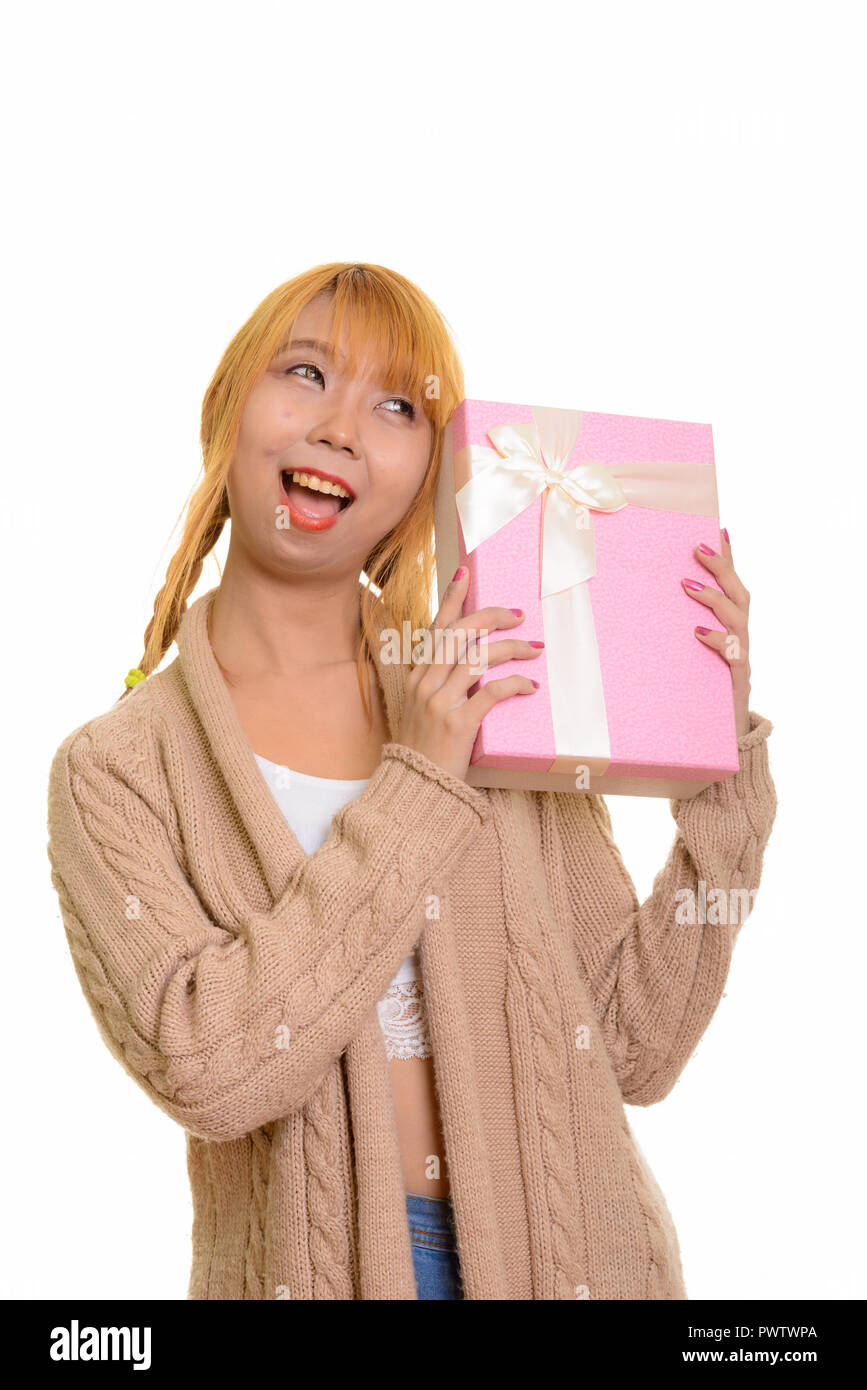 Young happy Asian woman smiling and guessing gift box - Stock Image