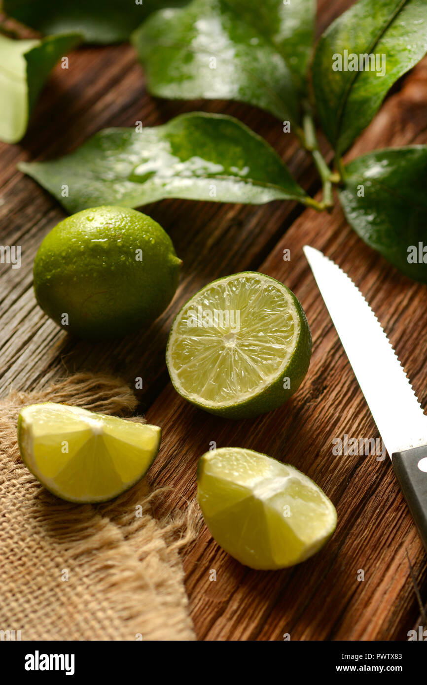 lime fruits with leaves on wooden table - tropical fruit with antioxidant properties - closeup - Stock Image