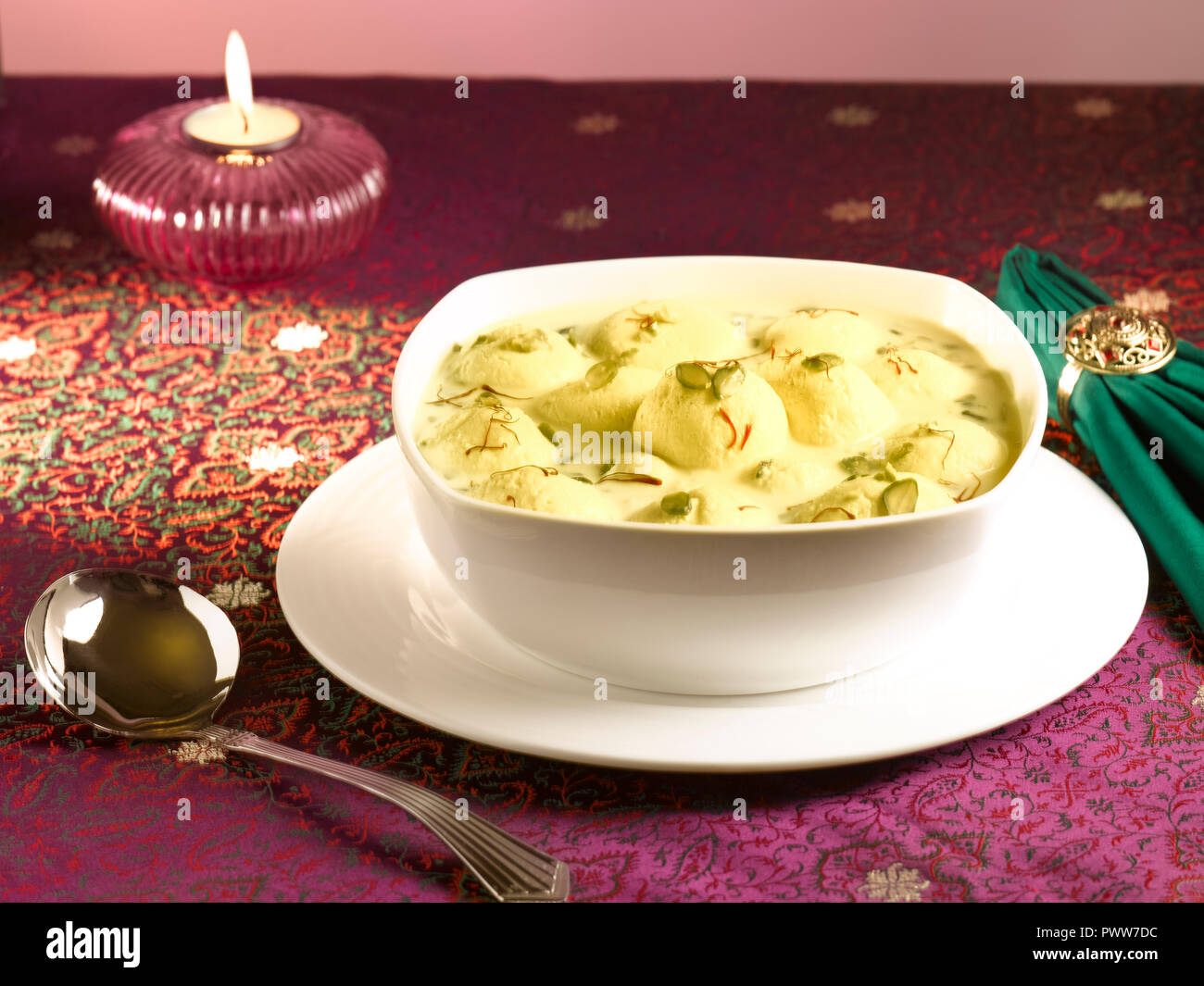 RASMALAI, AN INDIAN DESSERT MADE FROM COTTAGE CHEESE SOAKED IN SWEET SAFFRON MILK AND GARNISHED WITH PISTACHIO - Stock Image