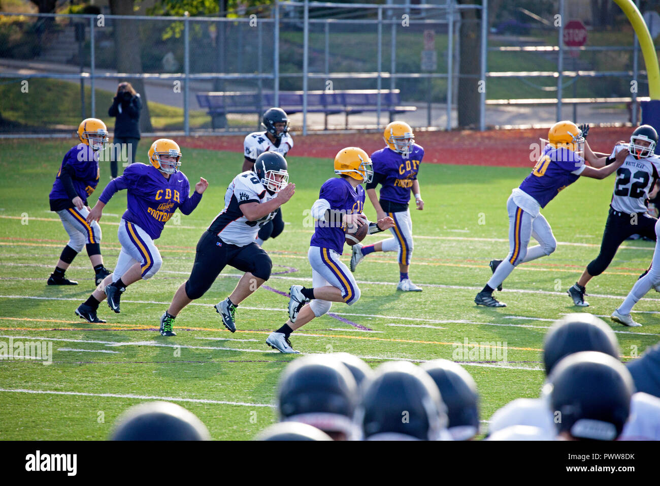 Cretin-Durham High School quarterback running ready to pass the ball while White Bear school defenseman is ready to pounce. St Paul Minnesota MN USA - Stock Image