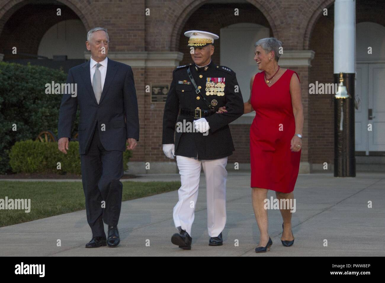 From left, Secretary James N. Mattis, Department ofDefense, Commandant of the Marine Corps Gen. Robert B. Neller, and D'Arcy Neller walk down center walk during an evening parade at Marine Barracks Washington, Washington, D.C., June 30, 2017. Neller hosted the parade and Mattis was the guest of honor. Stock Photo