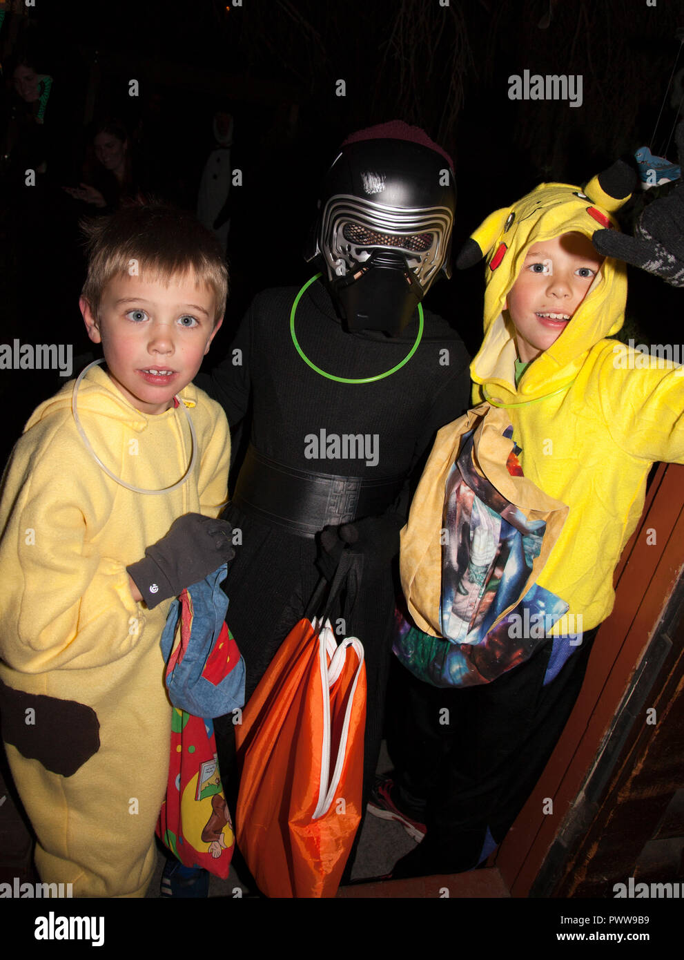 Darth Vader brings his Halloween costumed accomplices out for a night of Halloween tricks or treats and candy filled bags. St Paul Minnesota MN USA - Stock Image