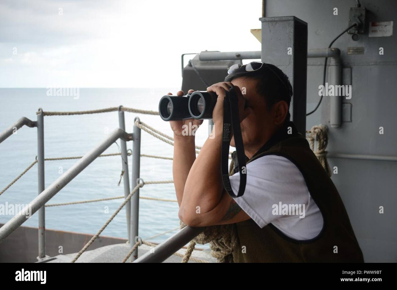 NOUMEA, New Caledonia (July 03, 2017) Sison Emerson, Able-Bodied Watchstander onboard USNS Sacagawea (T-AKE 2), stands watch off shore Noumea, New Caledonia in support of Koa Moana 17, July 3. Koa Moana 17 is designed to improve theater security, and conduct law enforcement and infantry training in the Pacific region in order to enhance interoperability with partner nations. ( Stock Photo