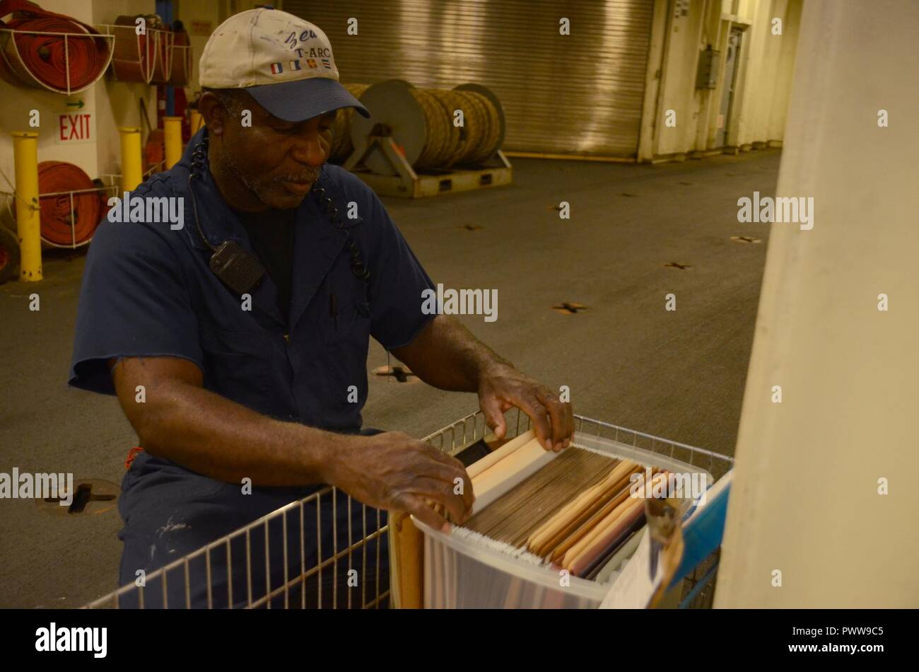 NOUMEA, New Caledonia (July 03, 2017) Joseph Celestine, Able-Bodied Seaman (maintenance) onboard USNS Sacagawea (T-AKE 2), files documents off shore Noumea, New Caledonia in support of Koa Moana 17, July 3. Koa Moana 17 is designed to improve theater security, and conduct law enforcement and infantry training in the Pacific region in order to enhance interoperability with partner nations. ( - Stock Image