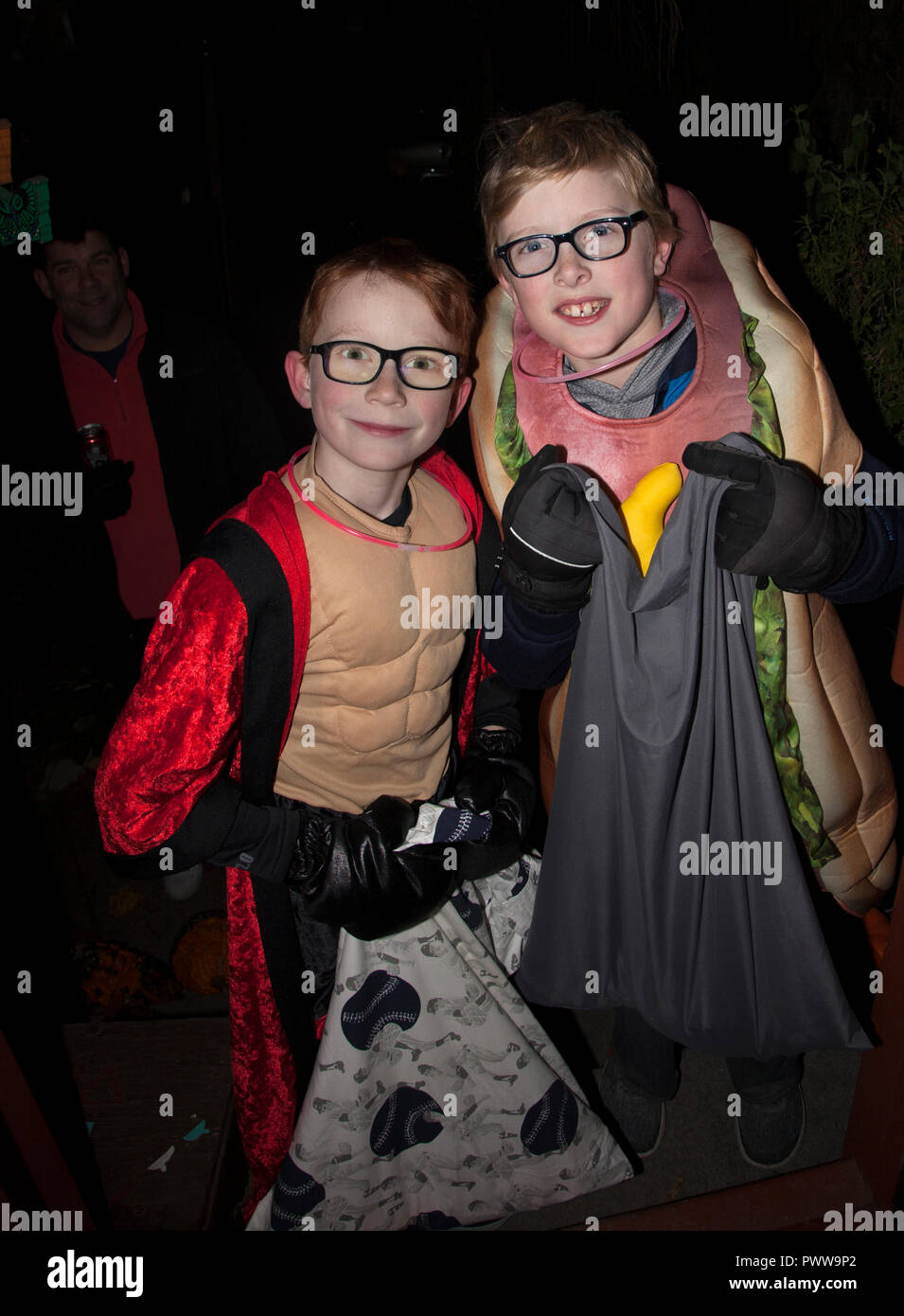 Two costumed brothers carry giant Halloween tricks or treats candy sacks door to door.   St Paul Minnesota MN USA - Stock Image