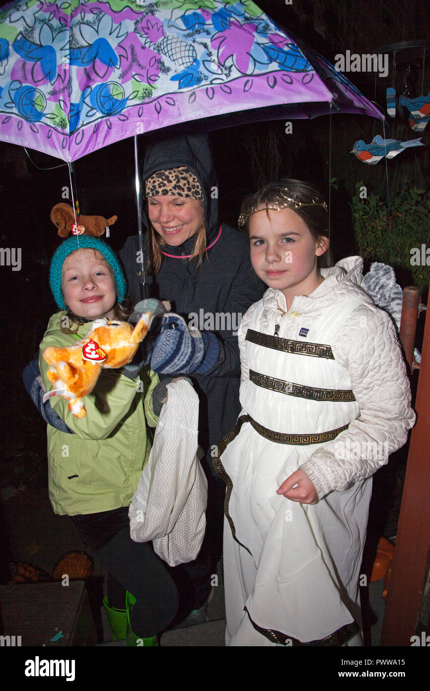 cbed964135f Mom and daughters under a violet and blue umbrella costumed for Halloween  trick or treating with