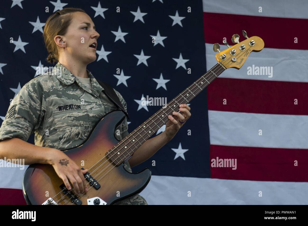Staff Sgt. Emily Wheaton, Pacific Air Force Band member, plays a guitar during a concert at the Celebrate America festival on Yokota Air Base, Japan, June 30, 2017. The day kicked off with the firecracker 5K run and a wide variety of activities to include a petting zoo, dance performaces, food and fireworks. - Stock Image