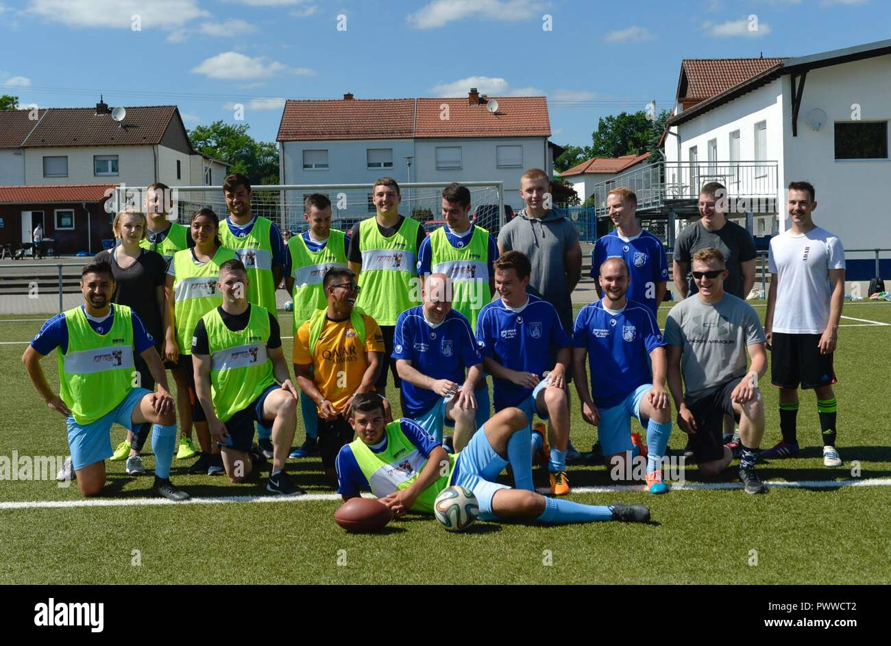 Ramstein Air Base Airmen and Fussballverein Ramstein Fußball Club A-Team pose for a photo during the Grassroots program sports day, at FV Olympia Field in Ramstein Misenbach, Germany, June 24, 2017. More than 25 Airmen and soccer players volunteered for the event to help build relations between service members and the local community. - Stock Image