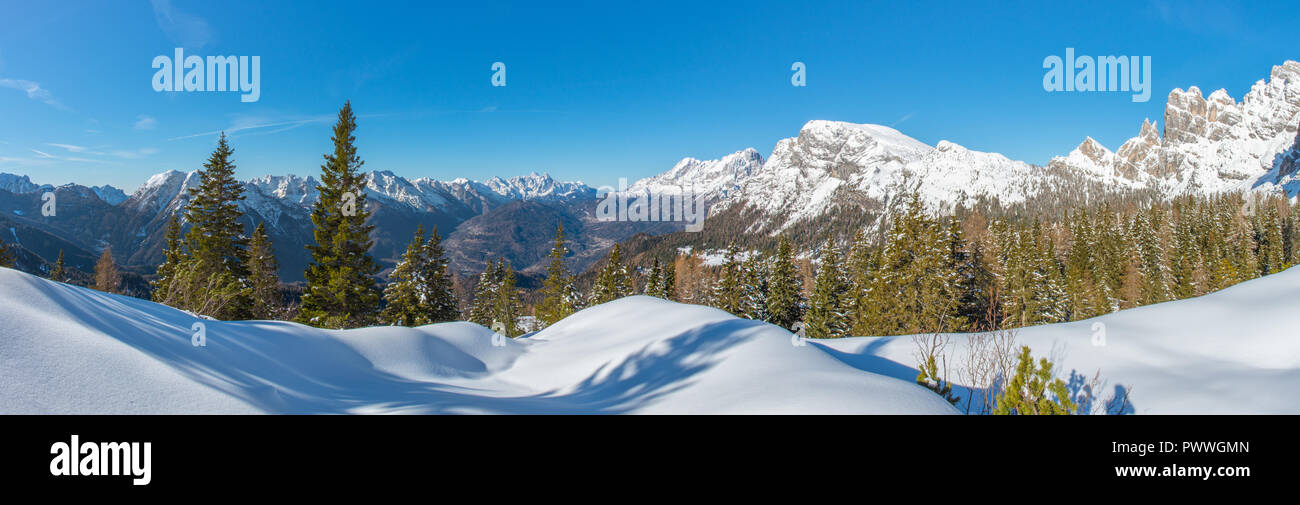 Panoramic view of fresh powder in the forest, snowcapped mountains and the valley bottom. Italian Alps winter, blue sky and some great snowshoeing. - Stock Image