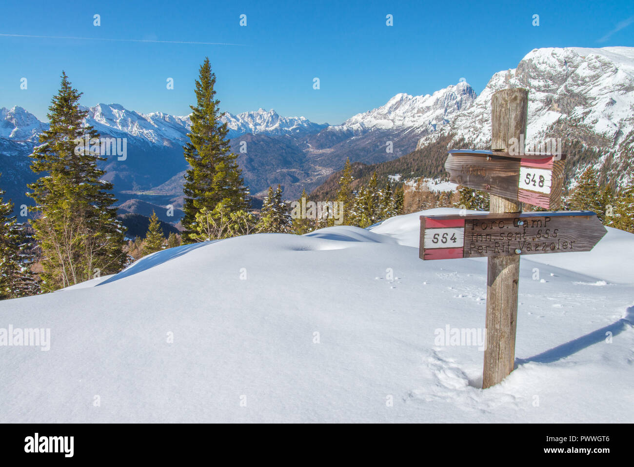 Trail marker, signpost pointing the way towards the many trails of the southern Italian Alps. Snowshoeing, tracks on the snow, cloudless day. - Stock Image