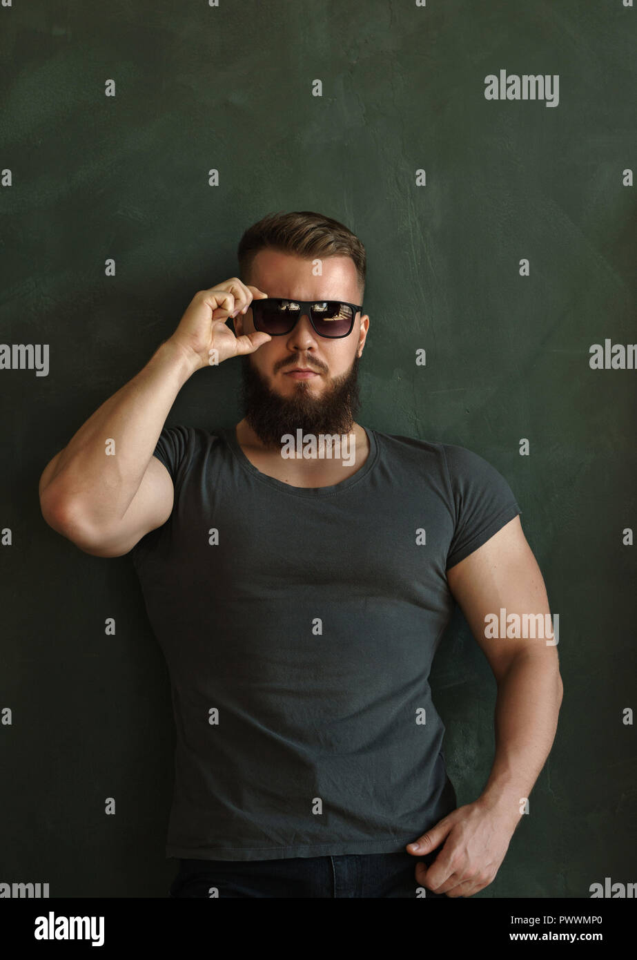 f212fa3e109f Bodybuilder in sunglasses portrait. Muscular man with a beard in a tight  t-shirt straightens his glasses. Stylish and sporty.