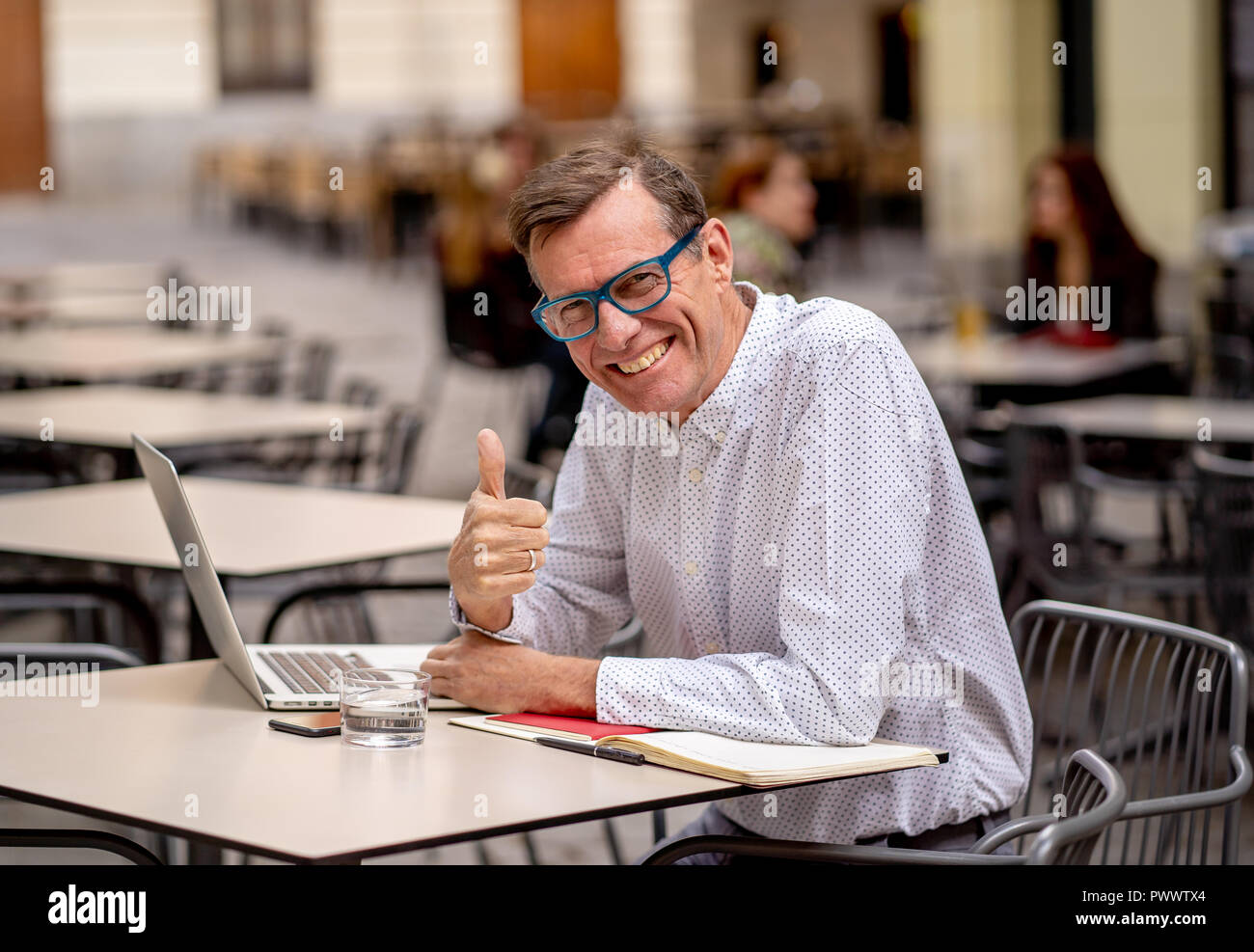 Cheerful Smiling Old Man Working On Computer While Having Coffee In