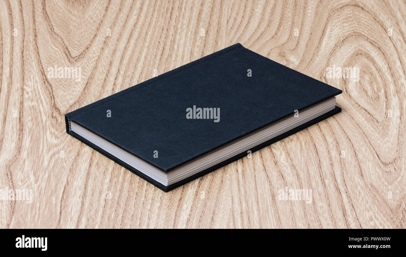 Black book on wooden table - Stock Image