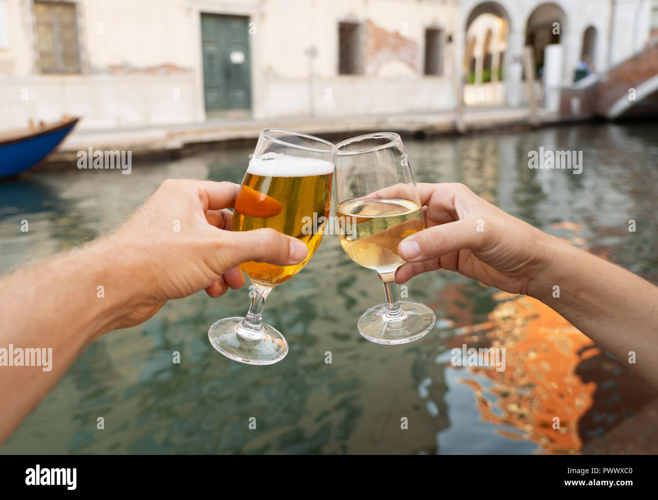 Two glasses of beer and wine, couple drinking by the canal in Venice romantic celebration of engagement or anniversary summer holidays and dating conc - Stock Image