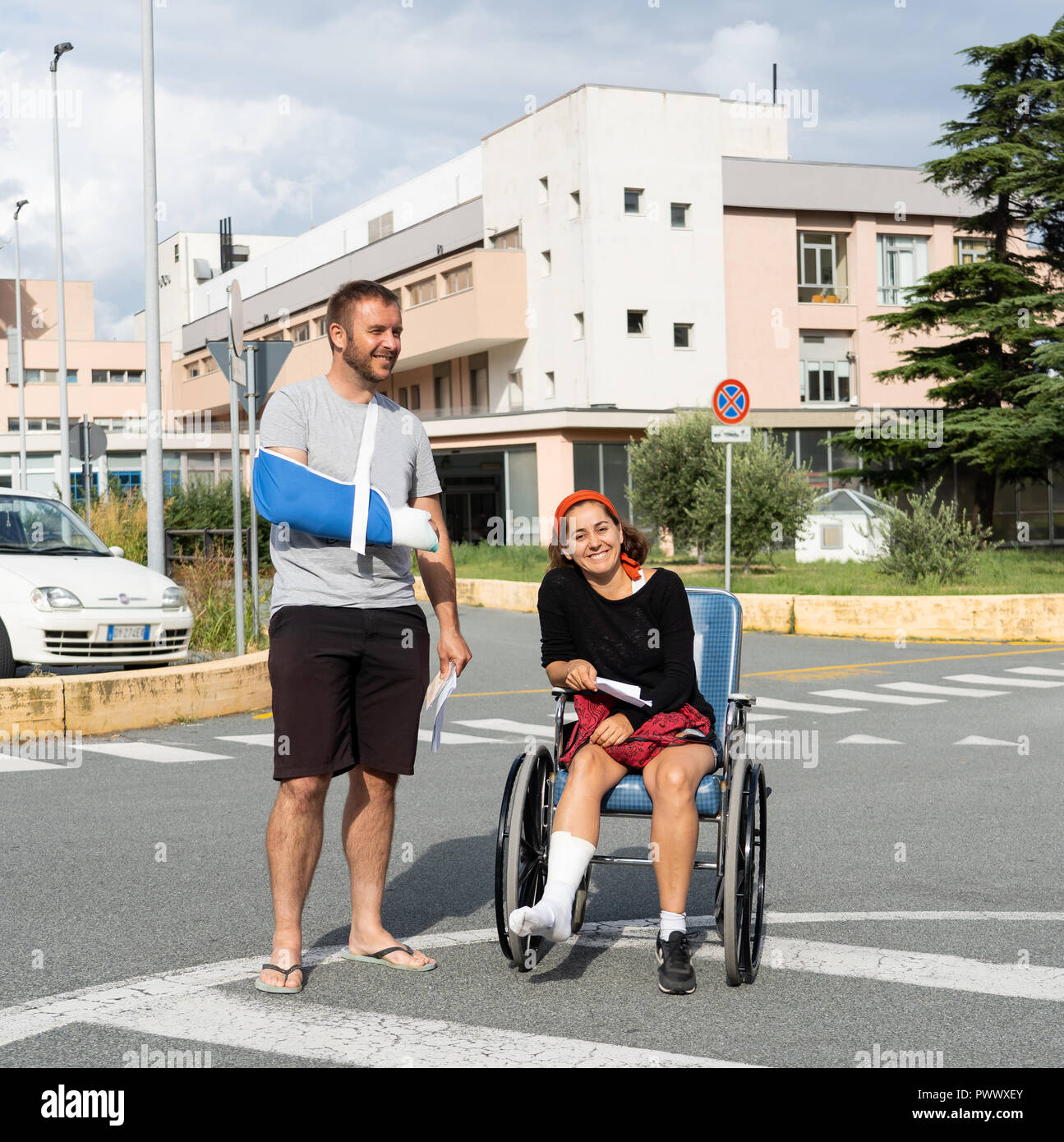 Young injured couple with broken foot and arm coming out of the hospital happy that their insurance paid the medical bills in travel health insurance  - Stock Image