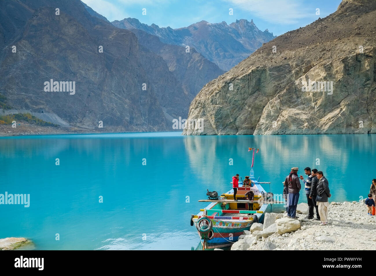 Gilgit Baltistan, Pakistan. October 28,2017 : People going to rent a boat at Attabad lake, with a view of mountains backdrop. Gojal, Hunza. - Stock Image