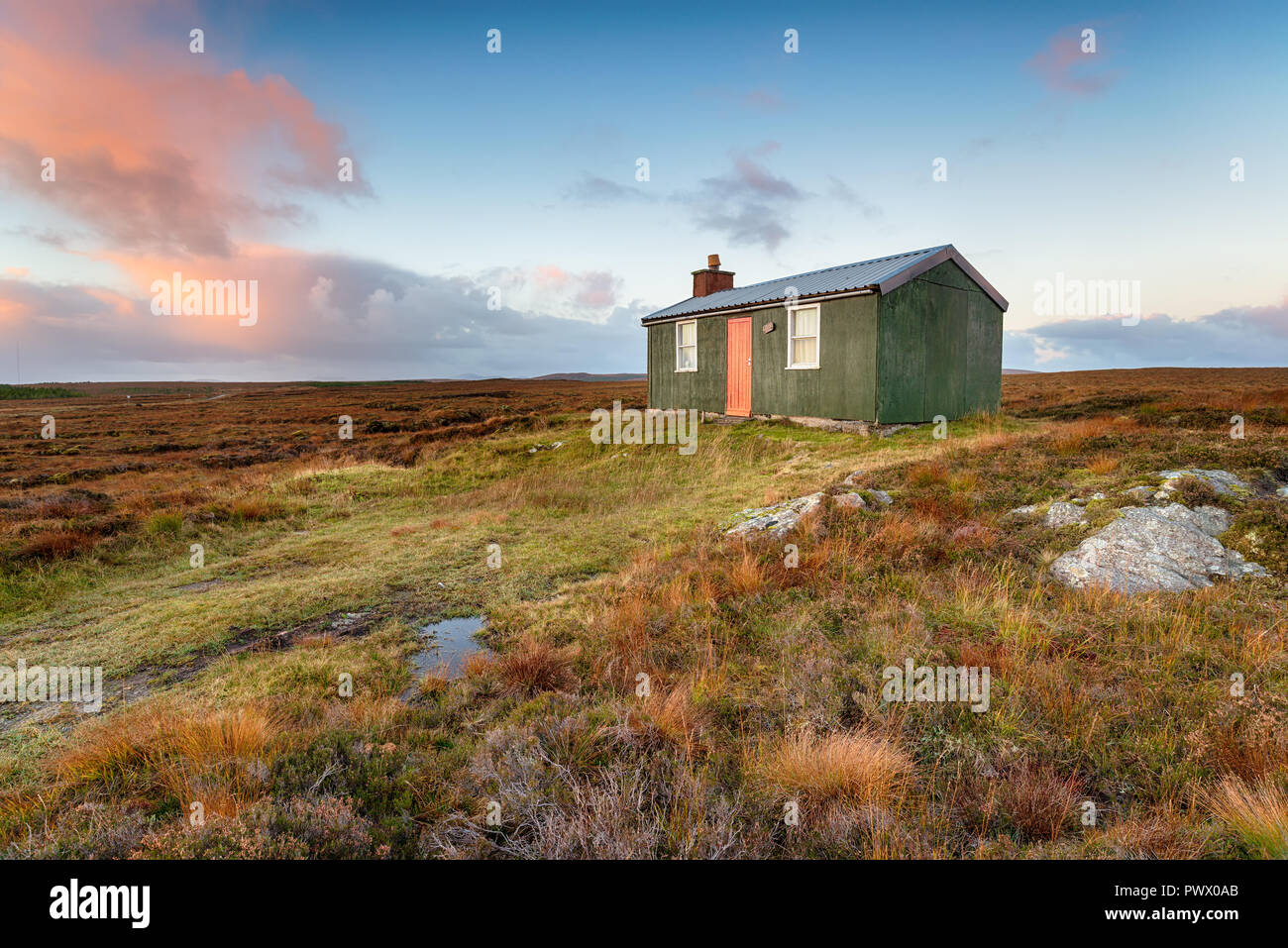 A tiny cottage or hut known as a shieling which is used for shelter while pasturing animals, on peat bog near Stornoway on the Isle of Lewis in Scotla Stock Photo