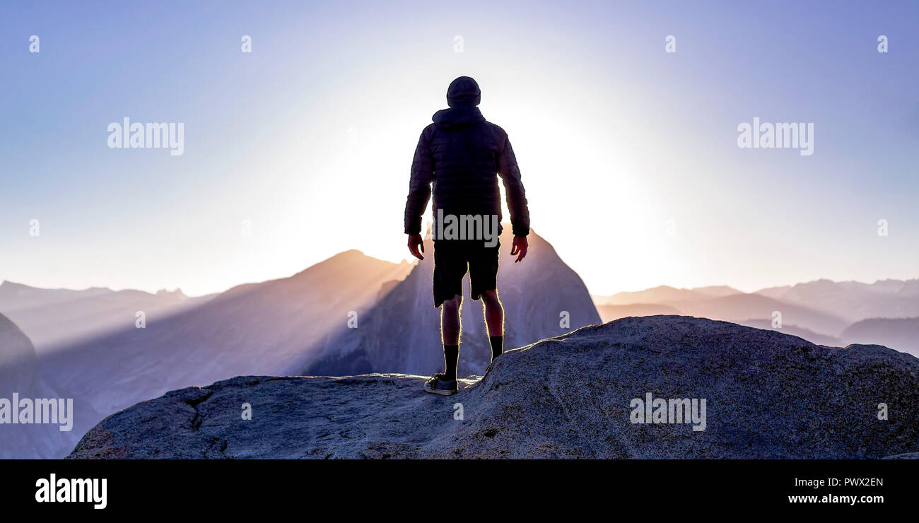 Man on a cliff with view of sun and mountains - Stock Image