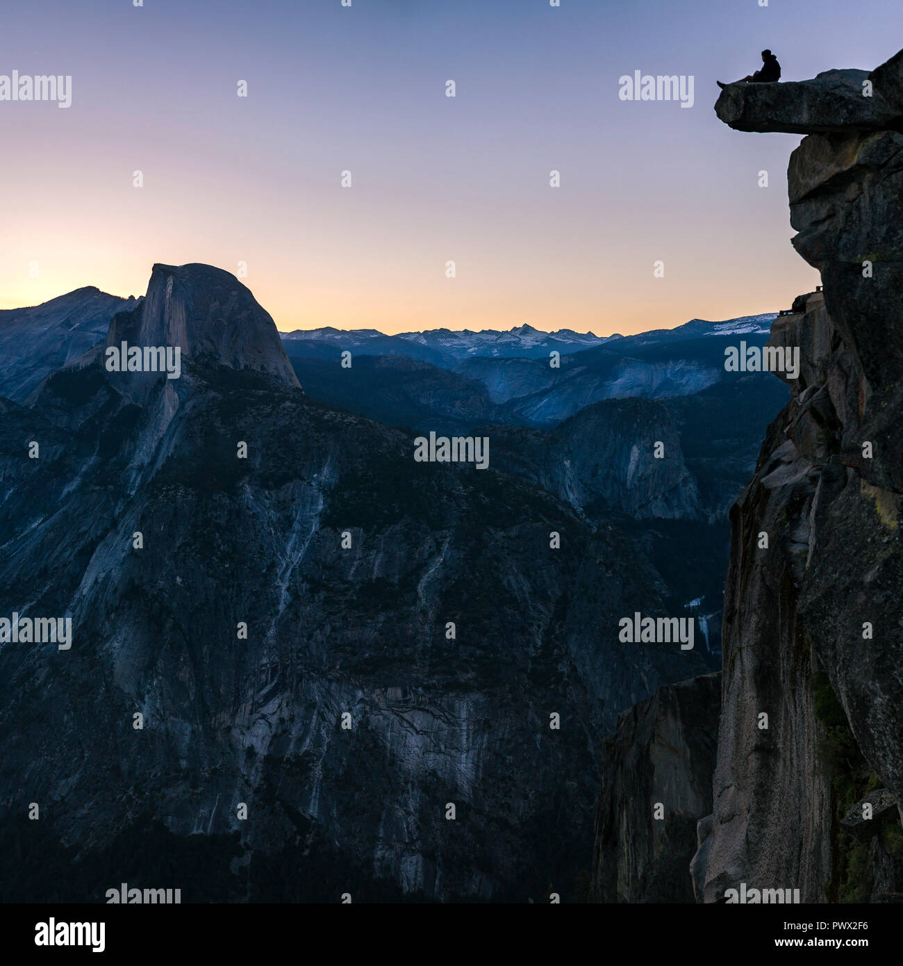 Man sitting at the edge of a cliff in Yosemite - Stock Image