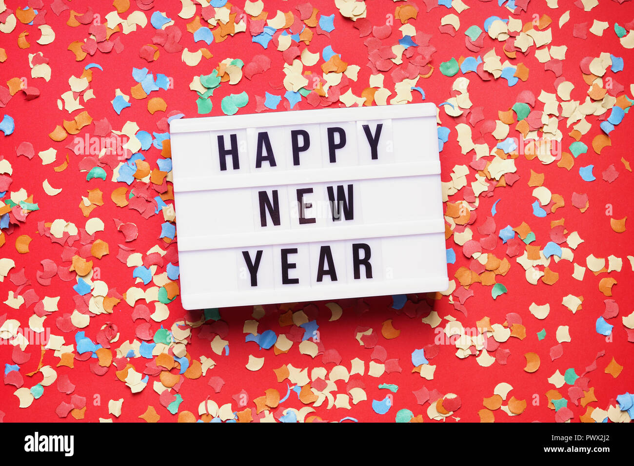 happy new year party celebration flat lay with confetti on red background - Stock Image