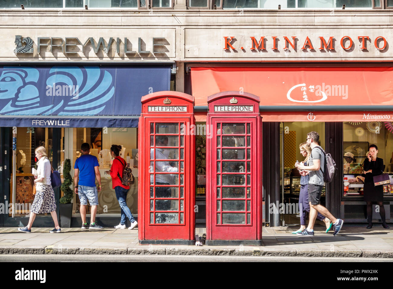 London England United Kingdom Great Britain West End St James's shopping district storefronts red telephone box public phone booth kiosk Giles Gilbert - Stock Image