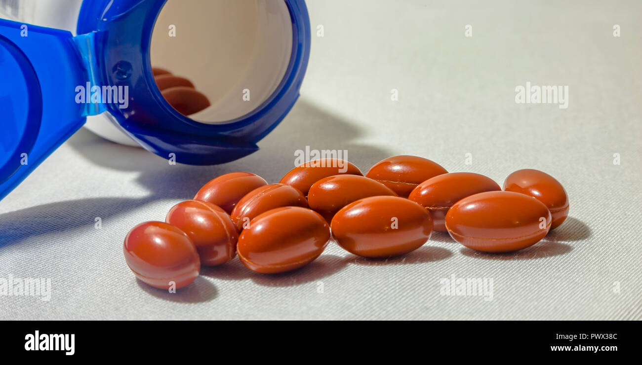 Oblong pills and open bottle on white background - Stock Image