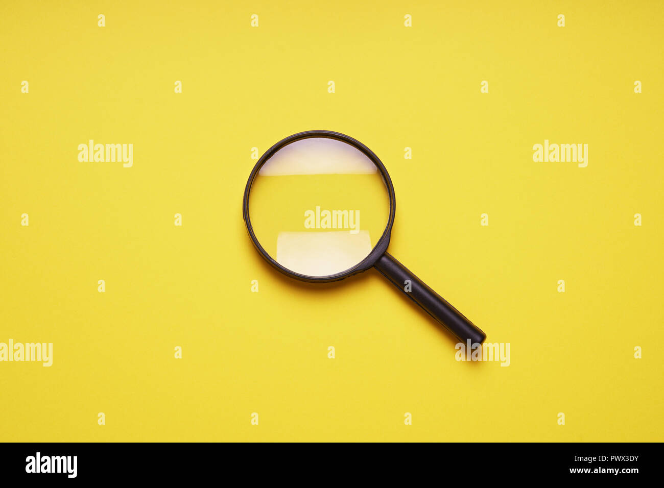 magnifying glass magnifier loupe search symbol on yellow background with copy space Stock Photo