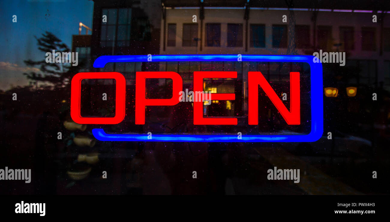 Red and blue open sign on a reflecive glass door Stock Photo