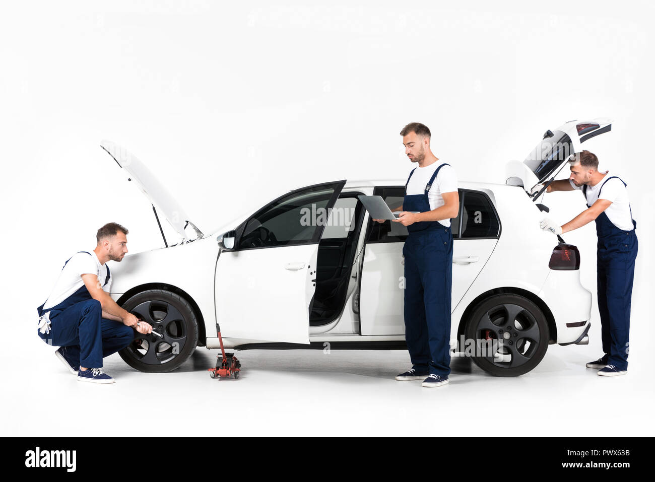 auto mechanic changing car tire, using laptop and looking in open car trunk on white - Stock Image