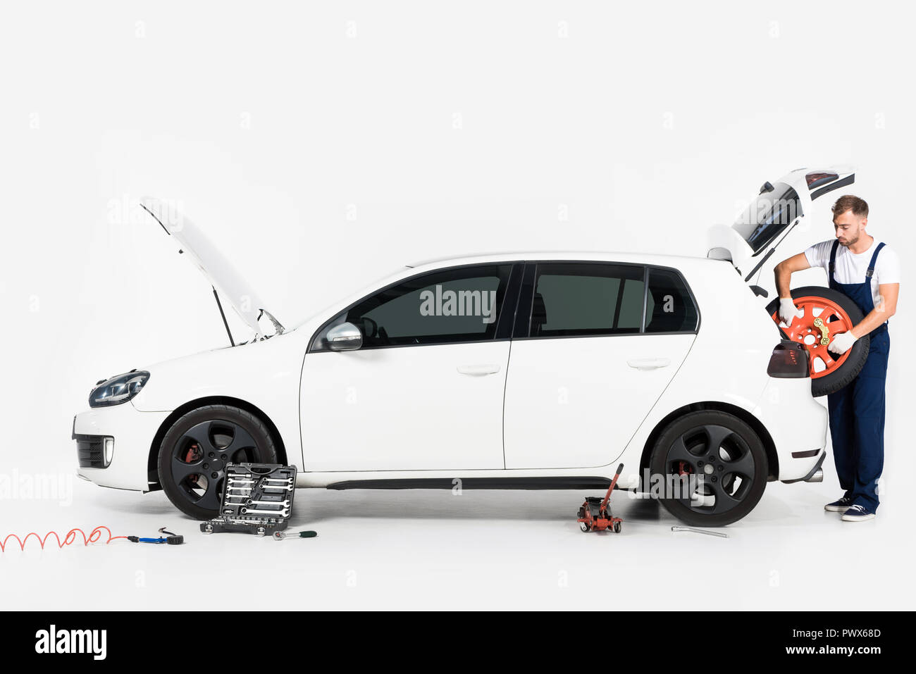 auto mechanic taking tire from car trunk on white - Stock Image