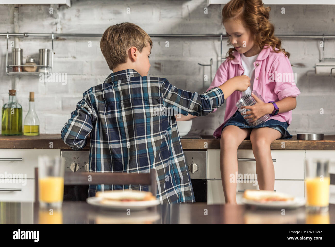 little brother and sister cooking breakfast together in morning - Stock Image