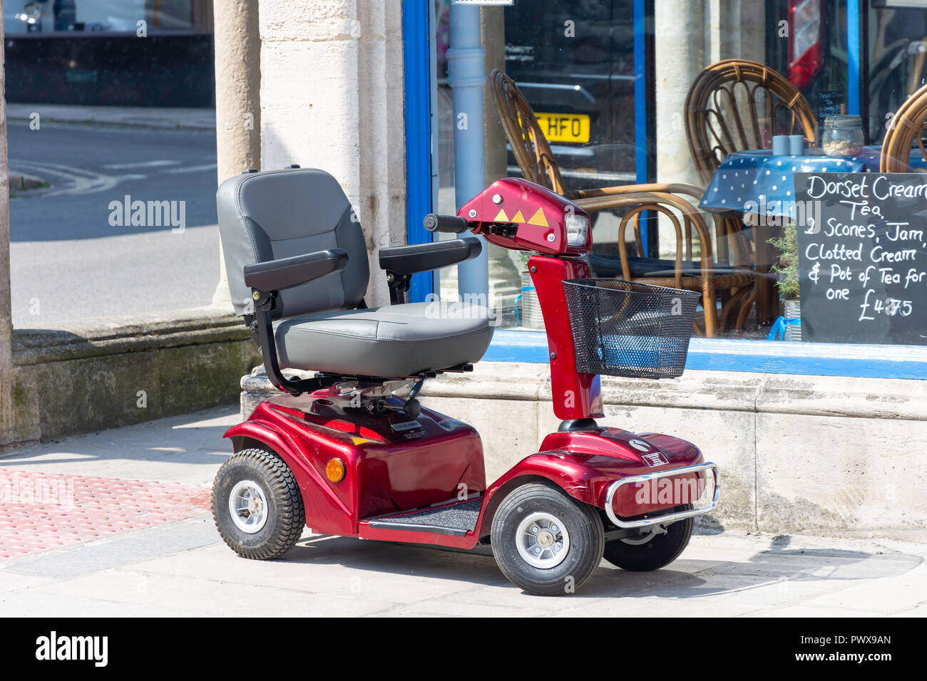 Mobility scooter parked outside cafe, High Street, Swanage, Isle of Purbeck, Dorset, England, United Kingdom - Stock Image