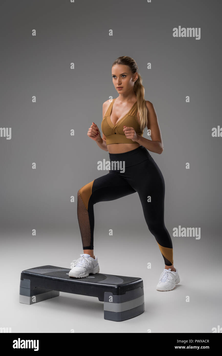 sportive young woman working out on step aerobics board on grey - Stock Image