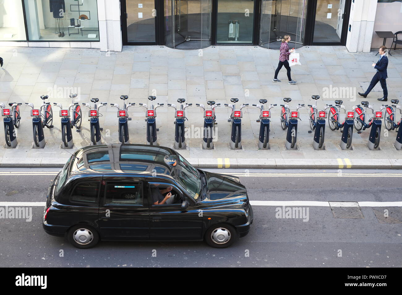 drone aerial photos of london black cab travels along a major A road in the city of London, with TFL boris Bikes/rent bikes racked up outside offices Stock Photo